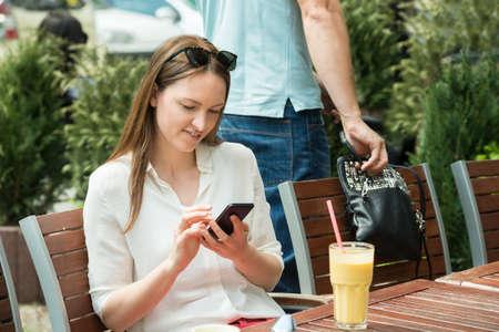 Männliche Dieb stiehlt Handtasche einer jungen Frau mit Handy Standard-Bild