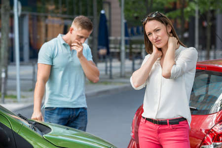 auto accident: Wounded Young Woman Standing On Street After Car Collision Stock Photo