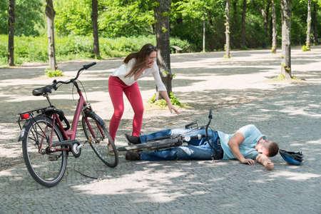 hombre cayendo: Mujer que consigue preocupado por Hombre que cae abajo mientras que monta la bicicleta