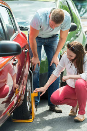two car garage: Young Couple Looking At Wheel Lock On Their Illegally Parked Car