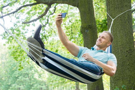 people relax: Young Happy Man Lying In Hammock Taking Picture With His Mobile Phone