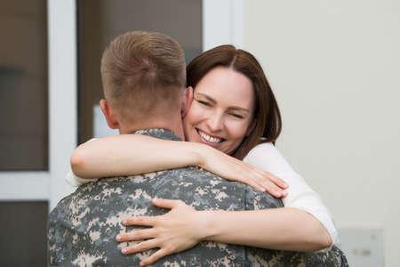 Retrato de la esposa feliz abrazando a su marido en el uniforme del Ejército Foto de archivo