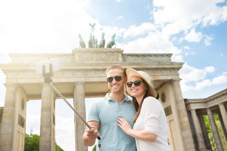 sticks: Young Happy Couple Taking Selfie At Brandenburg Gate