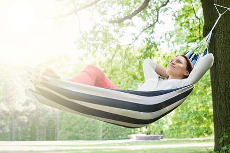Jonge Gelukkige Vrouw Ontspannen In Hangmat In Tuin Stockfoto