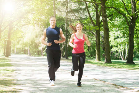 jogging track: Photo Of Young Happy Couple Jogging In Park Stock Photo