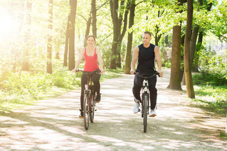 middle age: Young Happy Couple Riding Bicycles In Park
