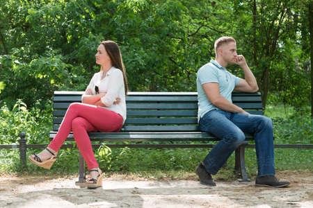 banc de parc: Contrarié Jeune couple assis sur un banc dans le parc Banque d'images