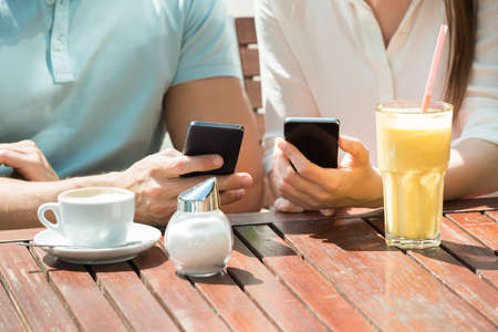 morning coffee: Close-up Of Young Happy Couple Sitting On Bench Using Mobile Phone