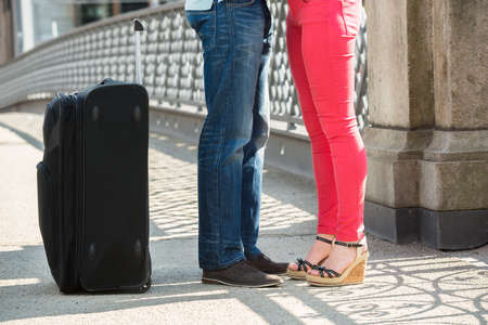 female legs: Low Section Of Couple Standing On Bridge With Luggage Stock Photo