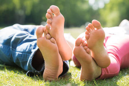 Close-up Of Couple Feet While Lying On Grass At Park