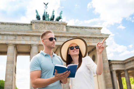 tourist guide: Young Couple Reading Tourist Guide In Front Of Brandenburg Gate Stock Photo