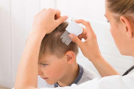 Close-up der weiblichen Arzt tun Behandlung auf Jungen Haar mit Kamm