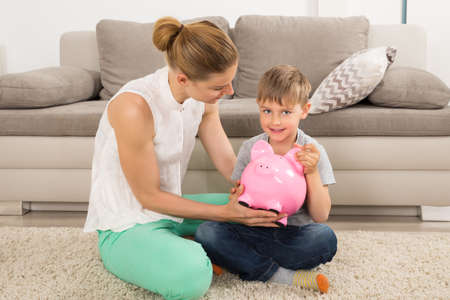 son deposit: Mother And Son Sitting On Carpet Holding Piggybank