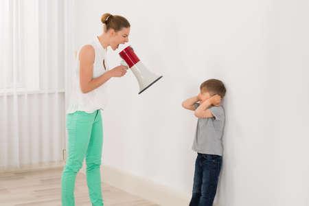 Mère criant à travers son Fils Megaphone Banque d'images