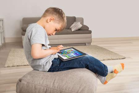 Boy Sitting On Cushion Playing Game On Digital Tablet