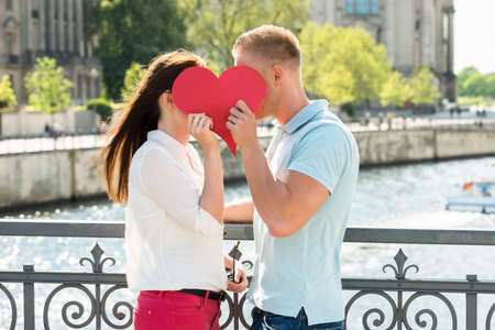 Side View Of Young Couple Kissing Behind Heart Shape Stock Photo