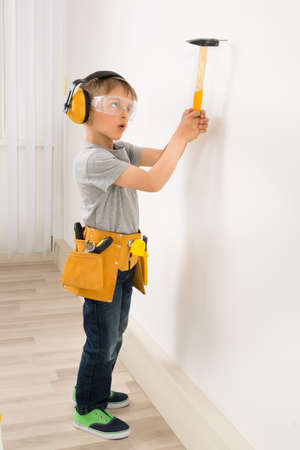 Cute Little Boy Hammering Nail In Wall At Home Stock Photo
