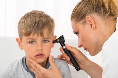 Primo Piano Di Dottoressa Esaminando orecchio del ragazzo con un otoscopio