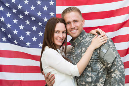 Portrait Of Young Male Soldier With His Wife In Front Of American Flag