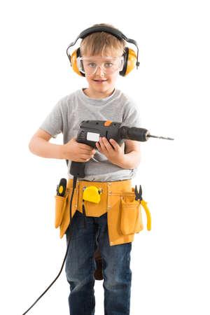 zapatos de seguridad: Retrato de muchacho feliz Holding perforación de la máquina sobre el fondo blanco Foto de archivo