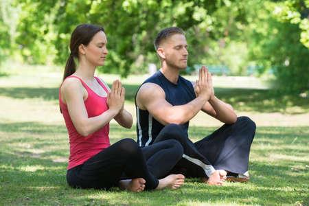 position d amour: Jeune couple Pratiquer le yoga dans le parc Au Matin