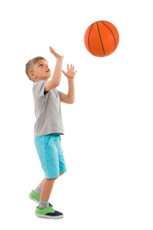Foto des Jungen Werfen Basketball über weißem Hintergrund
