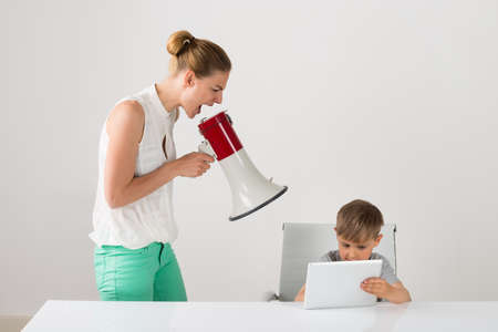 Frustrated Mother Shouting Through Megaphone To Boy Using Digital Tablet