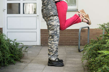 low section view: Low Section View Of Wife Embracing Her Husband In Army Uniform