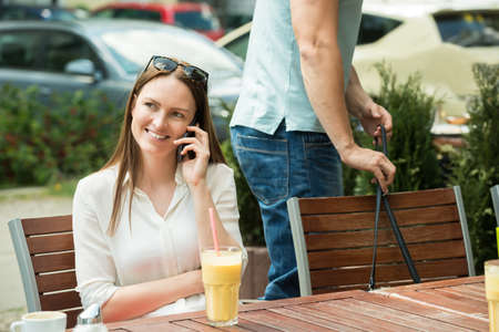 pickpocket: Male Thief Stealing Purse Of A Young Woman Using Mobile Phone