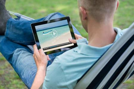 Man Watching Video On Digital Tablet While Relaxing In Hammock