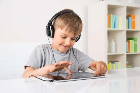 Little Boy feliz escuchando música en digital tablilla en el país Foto de archivo