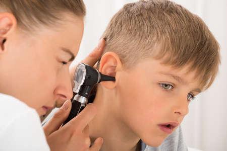 귀뚜라미와 소년의 귀를 검사하는 여성 의사의 근접 스톡 콘텐츠