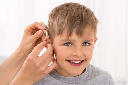 在微笑的男孩的耳朵上的醫生適合助聽器的特寫鏡頭