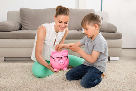 son deposit: Happy Mother Looking At Boy Inserting Coin In Piggybank Stock Photo