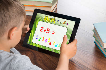 devices: Close-up Of Boy Solving Math Problem On Digital Tablet In Classroom