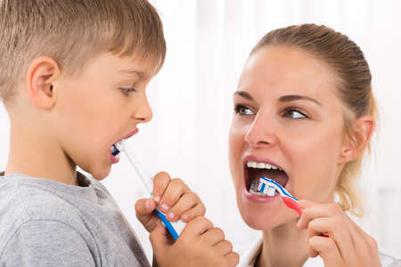 young boys: Close-up Of Young Female Doctor And Little Boy Brushing Teeth In Clinic Stock Photo
