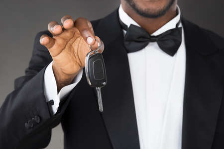doorkeeper: Close-up Of African Waiter Holding Car Key In Hands Stock Photo