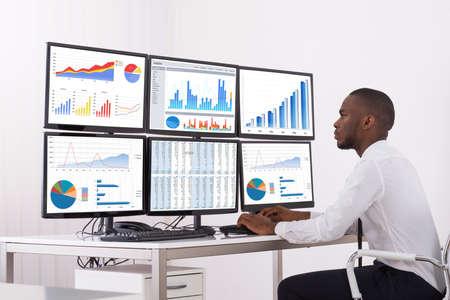 Jeune homme d'affaires analyse le graphique sur plusieurs ordinateurs au bureau