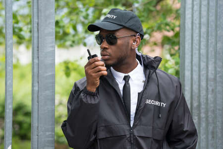talkie: Young Male Security Guard In Black Uniform Using Walkie-Talkie