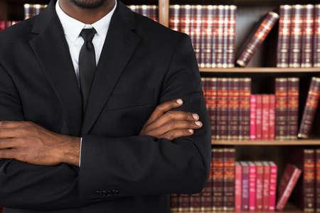 negras africanas: Primer plano de un abogado de sexo masculino con los brazos cruzados en la Oficina