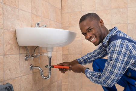 Young African Male Plumber Repairing Sink In Bathroom Reklamní fotografie