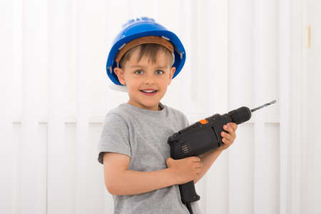 Portrait Of Happy Little Boy Holding Electric Drill Stock Photo