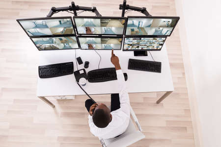 multiple: High Angle View Of Male Operator Pointing At CCTV Footage On Computer