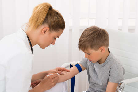 クリニックで小児患者の若い女性医師の血液サンプル