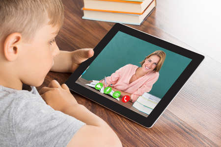 videoconferencing: Close-up Of Cute Little Boy Videoconferencing On Digital Tablet In Classroom