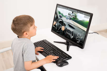 Little Boy Playing Car Game On Computer At Home Banque d'images