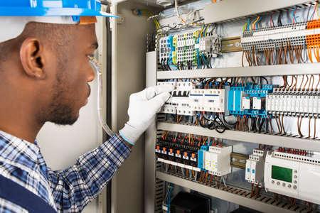 Fotografia Młody Afrykański Męski technik Sprawdza Fusebox Zdjęcie Seryjne
