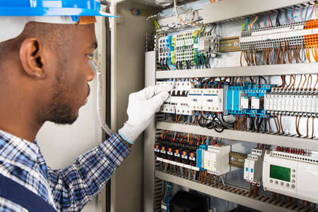 Photo Of Young African Male Technician Checking Fusebox Stock Photo