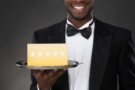 restaurant rating: Portrait Of African Waiter Holding Plate With Star Rating Stock Photo
