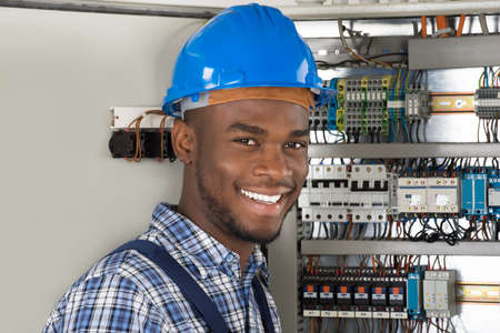 happy african: Male Technician Holding Clipboard While Examining Fusebox Stock Photo